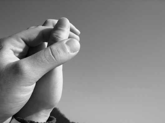 grayscale photography of human hand holding hands